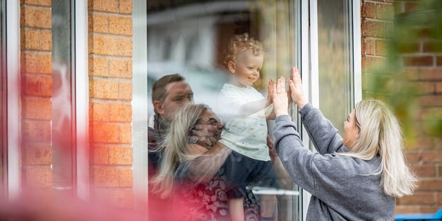 The mom-of-one managed to visit the tot through the safety of a window and placed her hand on his in heartbreaking pictures captured in May.