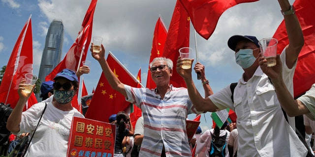 Pro-China supporters holding Chinese national flags, toast during a rally to celebrate the approval of a national security law for Hong Kong, in Hong Kong, on Tuesday. (AP)