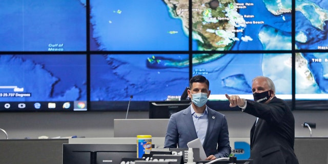 Miami-Dade County Mayor Carlos Gimenez, right, gives a tour to Acting Secretary of Homeland Security, Chad Wolf, of the Miami-Dade Emergency Operations Center, June 8, in Doral, Fla.