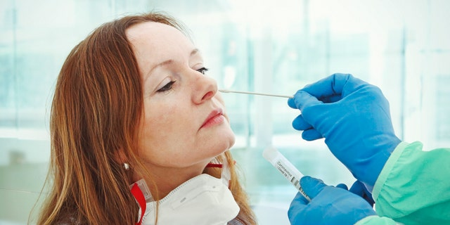 A medic takes a nasal swab from a patient for coronavirus testing. (iStock)