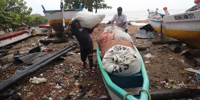 Fishermen load their nets onto a boat to keep them safe by the shores of the Arabian Sea in Mumbai, India, June 3.