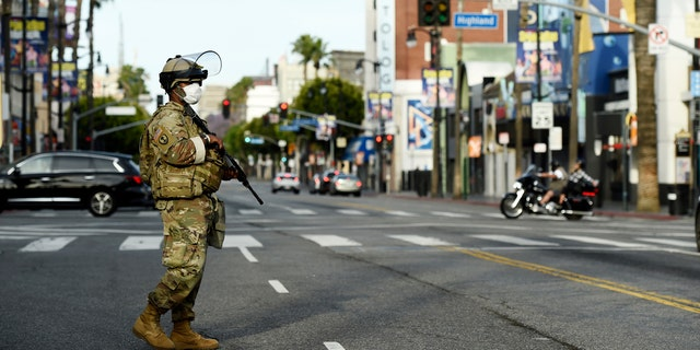 A U.S. National Guard soldier watches over Hollywood Blvd., Sunday, May 31, 2020, in Los Angeles.