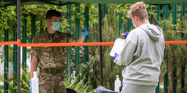 Members of the military operate a walk-in mobile COVID-19 testing center at Spinney Hill Park in Leicester, England, on Monday. (AP/PA)