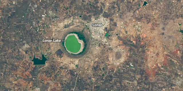 In this NASA photo from May 25, 2020, Lonar Lake can be seen with a green color at the surface.