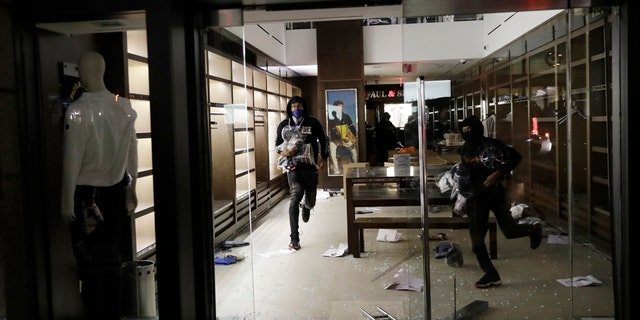 People carry merchandise out of a store that was broken into in New York, Monday, June 1, 2020. (AP Photo/Seth Wenig)