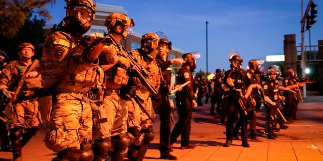 Security Police Officers with the Air National Guard stand with Louisville Metro Police officers during a protest against the deaths of Breonna Taylor by Louisville police and George Floyd by Minneapolis police, in Louisville, Ky., May 31, 2020.