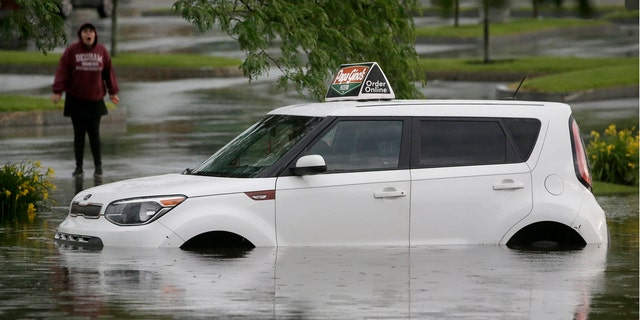 A woman speaks to a person in a vehicle stranded in water, Sunday, June 28, 2020, on a flooded street in Norwood, Mass.