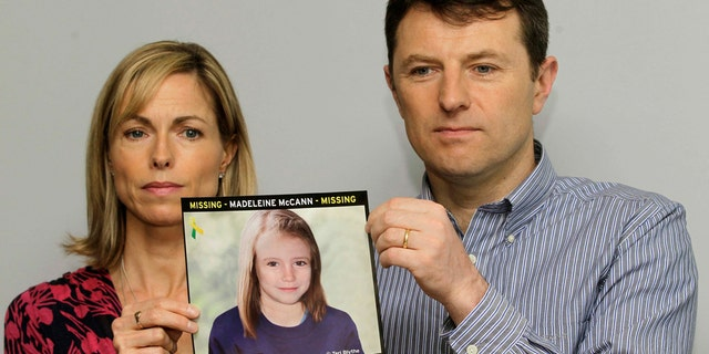 In this May 2, 2012 file photo, Kate and Gerry McCann pose for the media with a missing poster depicting an age progression computer-generated image of their daughter Madeleine at nine years of age.