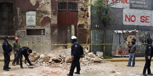 A policeman removes rubble from a building damaged by an earthquake in Oaxaca, Mexico, June 23.