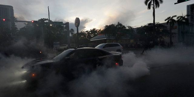 A protester does a burnout as he and others demonstrate over the death of George Floyd, Sunday, May 31, 2020, in Miami.