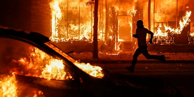 A protester runs past burning cars and buildings on Chicago Avenue, May 30, in St. Paul, Minn. (AP Photo/John Minchillo)