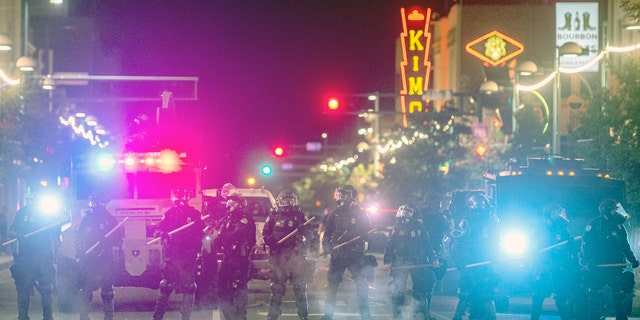 Police in riot gear prepare to clear downtown Albuquerque, N.M., early Monday, June 1, 2020.