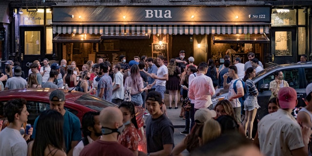 People drink outside a bar during the reopening phase following the coronavirus disease (COVID-19) outbreak in the East Village neighborhood in New York City, U.S., June 12, 2020. Picture taken June 12, 2020. REUTERS/Jeenah Moon