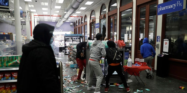People grab items inside a pharmacy that had its windows broken in New York, Monday, June 1, 2020.