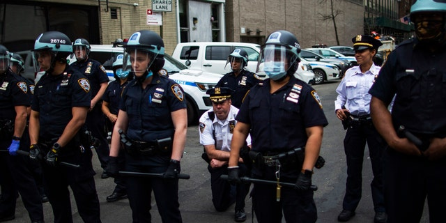 FILE - This file photo shows NYPD Deputy Chief McCarthy taking a knee near protesters and other officers as they take part in a march for George Floyd, Tuesday, June 2, 2020, in New York. Few of the officers are wearing face masks while on-duty. (AP Photo/Eduardo Munoz Alvarez)