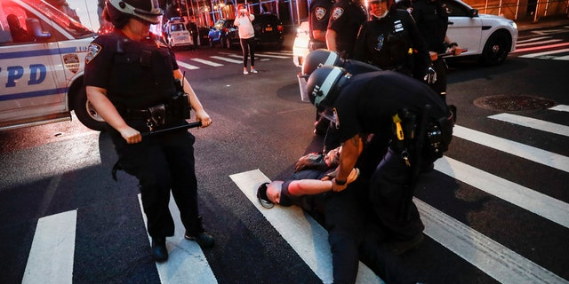 A protester is arrested by NYPD officers on Park Avenue after violating curfew June 5, in the Manhattan borough of New York. Protests continued following the death of George Floyd who died after being restrained by Minneapolis police officers on May 25. (AP Photo/John Minchillo)