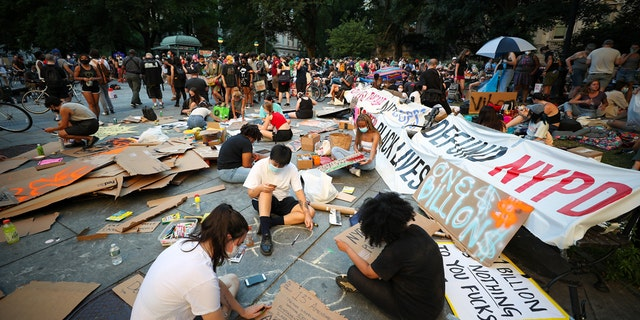 "A group of Black Lives Matter protesters prepare banners at City Hall across from One Police Plaza as part of the ""Defund NYPD"" and ""Occupy City Hall"" movement after spending the night on June 24, 2020, in New York City.<br>
