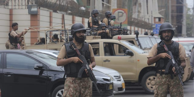 Security personnel surrounds the Stock Exchange Building after an attack in Karachi, Pakistan, on Monday. (AP)