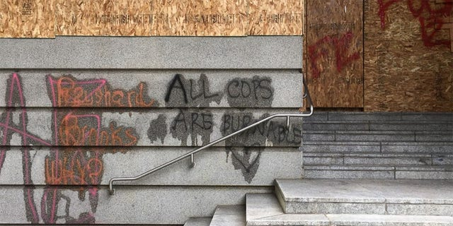 "Anti-cop graffiti reading ""All Cops Are Burnable"" with a heart drawn beneath it was found on a Portland building during a demonstration that turned violent on Saturday, police said,"