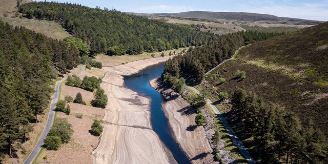 Dramatic images show how huge reservoir dwindled to a tiny stream in heat wave