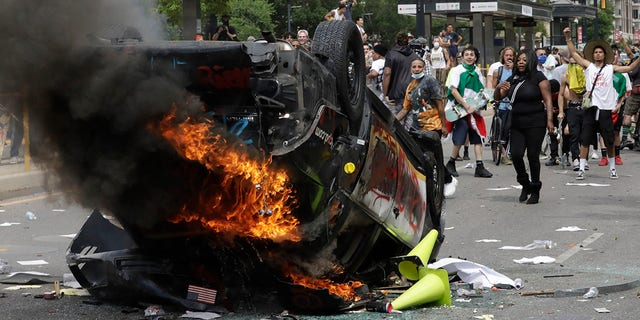 In this May 30, photo, protesters demonstrate as a Salt Lake City police vehicle burns, in Salt Lake City. Police have so far charged eight people in the incident. (AP Photo/Rick Bowmer)