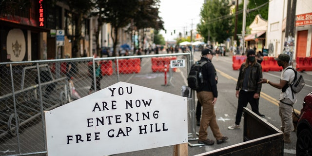 "A sign is seen on a barrier at an entrance to the so-called ""Capitol Hill Autonomous Zone"" on June 10, 2020 in Seattle, Washington."