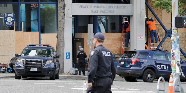 Workers put up plywood over the windows of a Seattle police precinct Monday, June 8, 2020, in Seattle. (AP Photo/Elaine Thompson)
