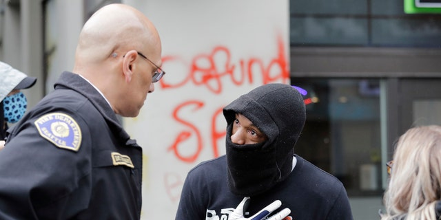 Demonstrator Keith Brown, right, talks with Seattle Fire Dept. Assistant Chief Willie Barrington as they plan to remove makeshift barricades protesters had put up in the streets next to a Seattle police precinct Tuesday, June 9, 2020, in Seattle. (AP Photo/Elaine Thompson)