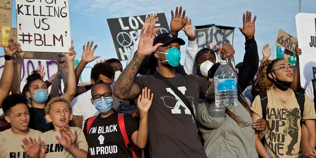 Portland Trail Blazers' Damian Lillard, center, joins other demonstrators in Portland, Ore., during a protest against police brutality and racism, sparked by the death of George Floyd, who died May 25 after being restrained by police in Minneapolis. (AP Photo/Craig Mitchelldyer)