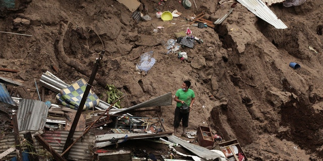 A man seeks to salvage some of his belongings from what used to be his home, destroyed by the waters of the Acelhuate River, in the New Israel Community of San Salvador, El Salvador, Sunday, May 31, 2020.