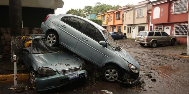 Vehicles stand damaged by an Acelhuate River flash flood at a neighborhood in San Salvador, El Salvador, May 31.