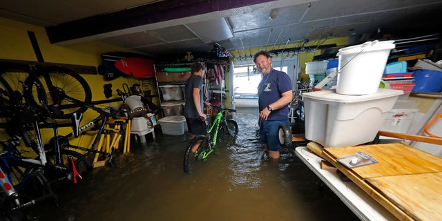 Rudy Horvath Jr., left, moves his bicycle from his home, a boat house in the West End section of New Orleans, as his father, Rudy Horvath Sr., right, looks on after it took on water from a rising storm surge from Lake Pontchartrain in advance of Tropical Storm Cristobal, Sunday, June 7, 2020.