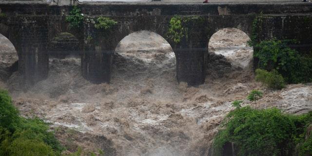 The swollen Los Esclavos River flows violently under a bridge during tropical storm Amanda in Cuilapa, eastern Guatemala, Sunday, May 31, 2020.