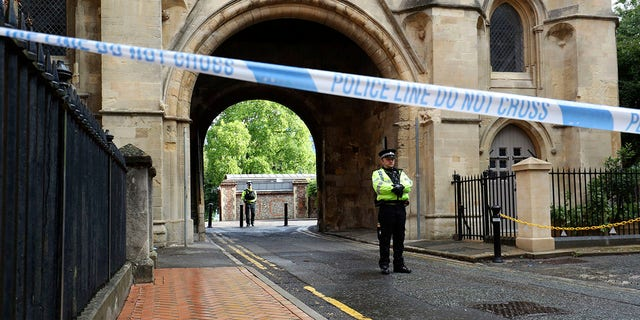 Police stand guard at the Abbey gateway of Forbury Gardens park in Reading town center Sunday following Saturday's stabbing attack in the gardens. (Jonathan Brady/PA via AP)