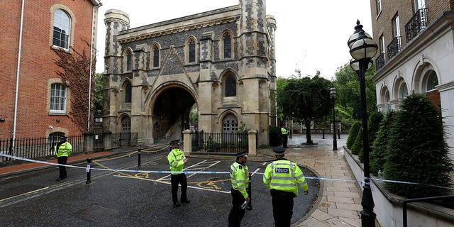 Police patrol the Abbey gateway of Forbury Gardens park in Reading town centre on Sunday following Saturday's stabbing attack in the gardens. (Jonathan Brady/PA via AP)