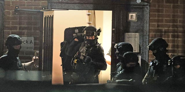 "Armed police officers work at a block of flats off Basingstoke Road in Reading after an incident at Forbury Gardens park in Reading, England, Saturday, June 20, 2020. Several people were injured in a stabbing attack on Saturday, and British media said police were treating it as ""terrorism-related."" (Steve Parsons/PA via AP)"