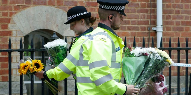 Police officers collecting flowers left at the Abbey gateway of Forbury Gardens on Sunday, one day after the stabbing attack. (AP Photo/Alastair Grant)
