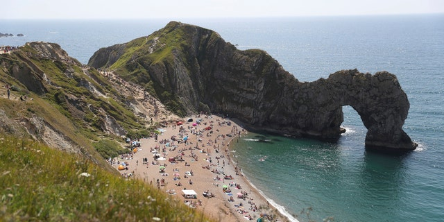 People relax on the beach of Durdle Door beach, as the public are being reminded to practice social distancing following the relaxation of coronavirus lockdown restrictions, near Lulworth in Dorset, England, Saturday May 30, 2020.