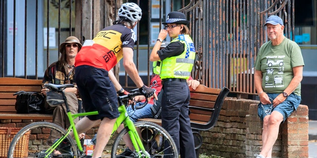 A Police Community Support Officer talks to people as they social distance in York, following the introduction of measures to bring England out of lockdown, in York, England, June 1.
