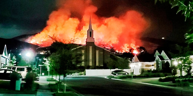 The Traverse Fire burns behind homes in Lehi, Utah, Sunday, June 28, 2020. Officials say fireworks caused the wildfire and forced evacuations early Sunday morning.