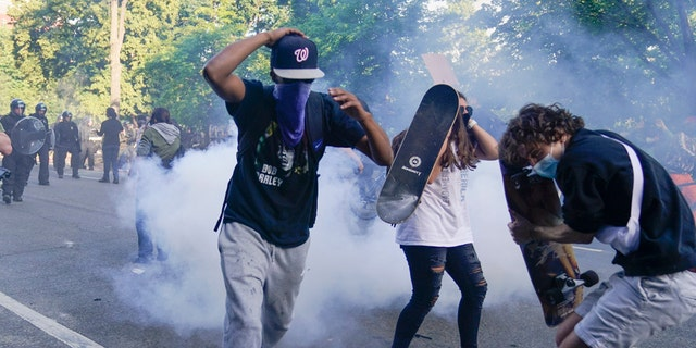 Demonstrators, who had gathered to protest the death of George Floyd, begin to run from tear gas used by police to clear the street near the White House in Washington, Monday, June 1, 2020. (Associated Press)