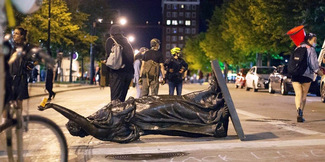 """Wisconsin's """"Forward"""" statue lies in the street on Capitol Square in Madison on Tuesday. The statue has since been recovered, officials said. (Emily Hamer/Wisconsin State Journal via AP)"""