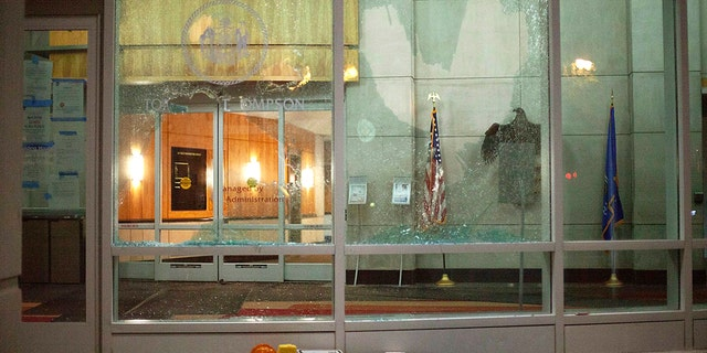 The windows of the Tommy G. Thompson Center on Public Leadership in Madison are shattered during demonstrations Tuesday. Evers said the damage to state property is still being assessed. (Emily Hamer/Wisconsin State Journal via AP)
