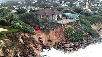 Australian homes teetering on cliff as waves lash coastline