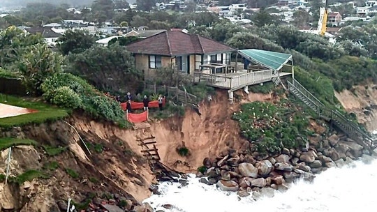 Australian homes teetering on cliff as waves lash coastline
