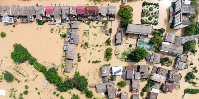 In this aerial photo released by Xinhua News Agency, a village is flooded in Sanjiao Township of the Yongxiu County in eastern China's Jiangxi Province July 13.