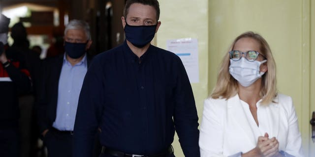 Presidential candidate Rafal Trzaskowski accompanied by his wife Malgorzata arrives to cast his vote during the presidential election runoff in Rybnik, Poland, Sunday, July 12, 2020. Voting started Sunday in Poland's razor-blade-close presidential election runoff between the conservative incumbent Andrzej Duda and liberal, pro-European Union Warsaw Mayor Rafal Trzaskowski.