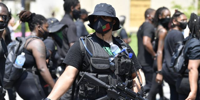"""An armed member of the """"NFAC"""" scans the crowd during a march through downtown toward the Hall of Justice in Louisville, Ky., Saturday, July 25, 2020. Hundreds of activists demanded justice for Breonna Taylor during the demonstrations in her hometown that drew counter-protesters from a white militia group. Taylor, a 26-year-old EMT, was fatally shot when police officers burst into her Louisville apartment using a no-knock warrant during an investigation.(AP Photo/Timothy D. Easley)"""
