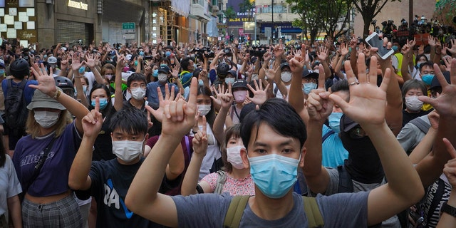 "Protesters against the new national security law gesture with five fingers, signifying the ""Five demands - not one less"" on the anniversary of Hong Kong's handover to China from Britain in Hong Kong, Wednesday, July. 1, 2020. Hong Kong marked the 23rd anniversary of its handover to China in 1997, and just one day after China enacted a national security law that cracks down on protests in the territory"