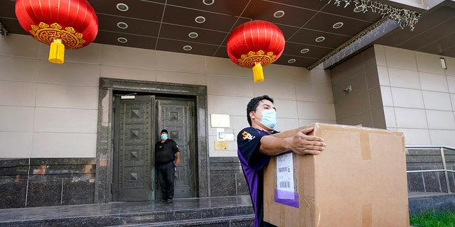A FedEx employee removes a box from the Chinese Consulate in Houston on Thursday. (Associated Press)